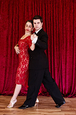 Tango dancers against red curtain - p1445m2128304 by Eugenia Kyriakopoulou