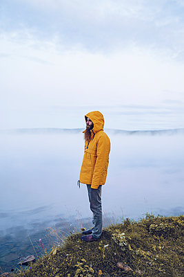 Sweden, Lapland, man with full beard wearing yellow windbreaker standing at water's edge looking at distance - p300m2059547 by CSSHOT