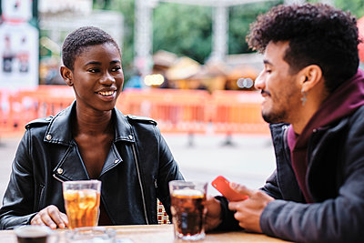 Smiling friends talking while sitting at sidewalk cafe - p300m2250162 by Alvaro Gonzalez