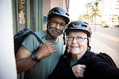 Smiling senior couple taking selfie with cycling helmet outside house - p426m2238921 by Maskot