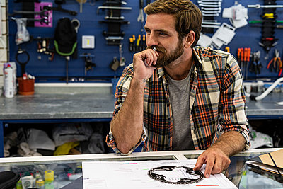 Owner sitting in workshop - p623m2214727 by Frederic Cirou