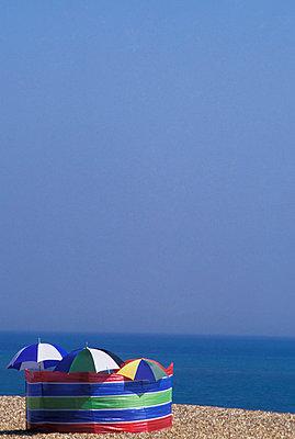 Windbreaker And Umbrellas On Pebble Beach - p644m728251 by Chris Parker
