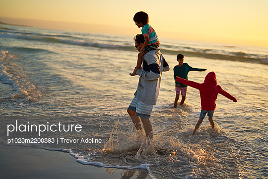 Family splashing and playing in ocean surf at sunset - p1023m2200893 by Trevor Adeline