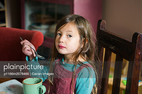 a cute messy girl with berry-stained lips eats at the table - p1166m2078466 by Cavan Images