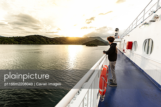 Teenager on boat traveling in between islands in New Zealand - p1166m2208049 by Cavan Images