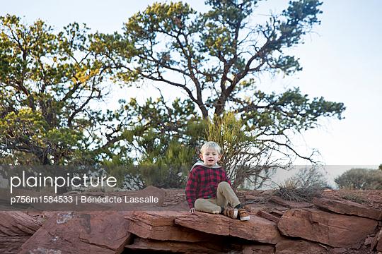Junge sitzt auf einem Felsen - p756m1584533 von Bénédicte Lassalle