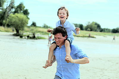 Father gives son a piggyback ride on the beach - p1258m2204698 by Peter Hamel