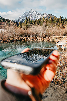 Mountain reflects in a smartphone - p1455m2081754 by Ingmar Wein