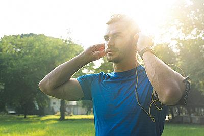 Sportive man wearing headphones, preparing for training in urban park - p300m1550203 by Steve Brookland