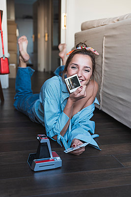 Portrait of happy young woman lying on the floor with instant photos of herself - p300m2029819 by Kike Arnaiz