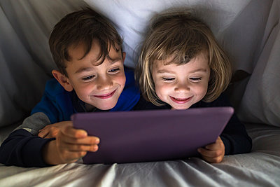 Portrait of happy brother and little sister lying side by side under a blanket using digital tablet - p300m2180271 by Josep Rovirosa