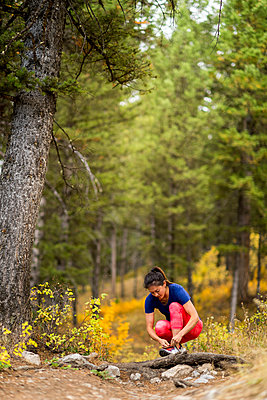 Woman tying shoes while trail running - p343m1585375 by Tyler D. Rickenbach