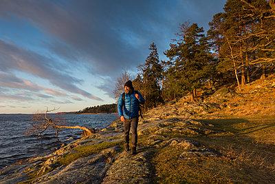 Man walking along coastline in Jarfalla, Sweden - p352m1536582 by Calle Artmark