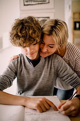 Smiling mother hugging son doing homework - p426m2279744 by Maskot