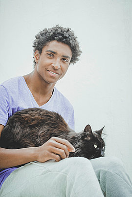 Young man and his cat - p445m1527839 by Marie Docher