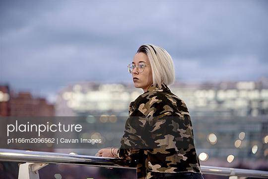 Trendy girl looking to the left on a bridge - p1166m2096562 by Cavan Images