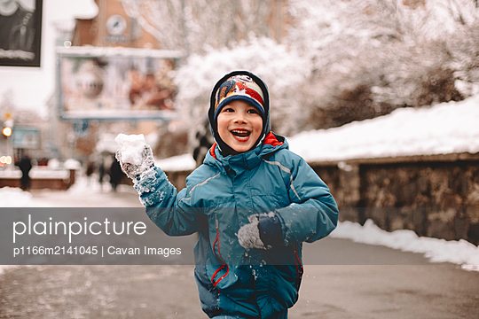 Happy boy holding snowball while running in street during winter - p1166m2141045 by Cavan Images