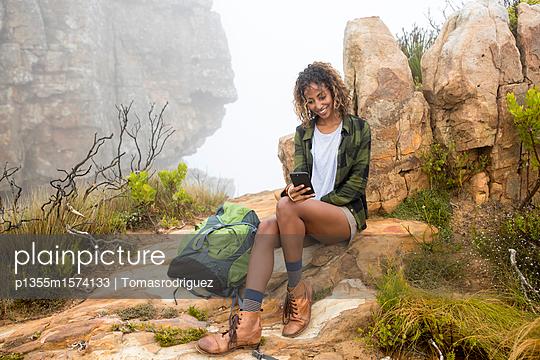 Junge Frau auf einer Wandertour liest eine SMS - p1355m1574133 von Tomasrodriguez