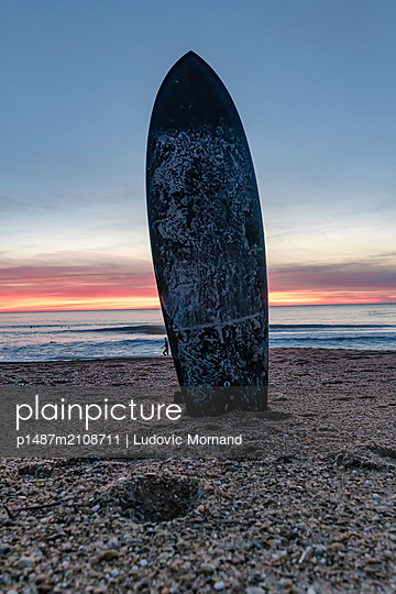 Surf board stuck in the sand at sunset - p1487m2108711 by Ludovic Mornand