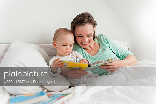 Mother and baby in bed reading picture book - p300m1587244 von Daniel Ingold