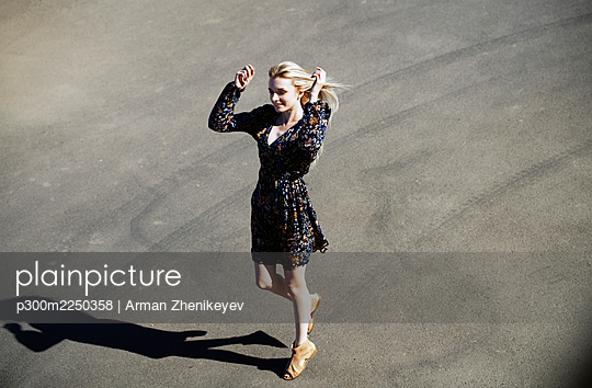 Beautiful young woman smiling while walking on road during sunny day - p300m2250358 by Arman Zhenikeyev