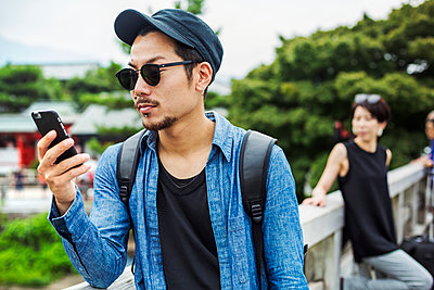 A man looking at his smart phone, a woman behind him. - p1100m1185880 by Mint Images