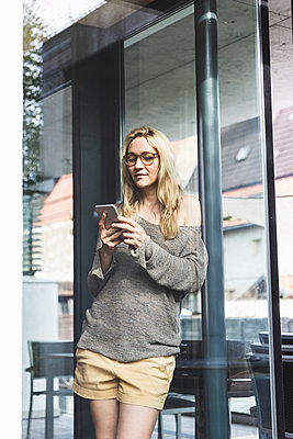 Portrait of blond mature woman standing in front of house looking at smartphone - p300m1587807 von Uwe Umstätter