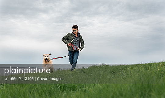 Teenage boy running up a grassy hill with his dog on cloudy day. - p1166m2113108 by Cavan Images