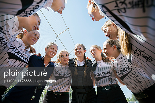 Coach and middle school girl softball team in huddle