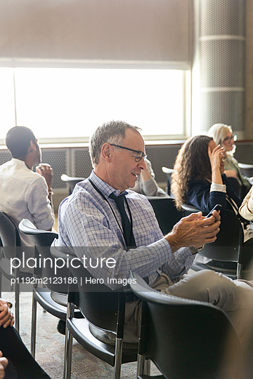 Senior businessman using smart phone in conference audience - p1192m2123186 by Hero Images