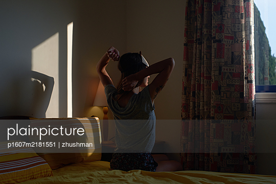 Woman in sleeping mask sit on bed and stretching her arms in the bedroom - p1607m2181551 by zhushman