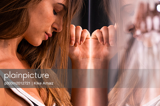 Serious attractive young woman with closed eyes leaning against glass pane - p300m2012721 von Kike Arnaiz