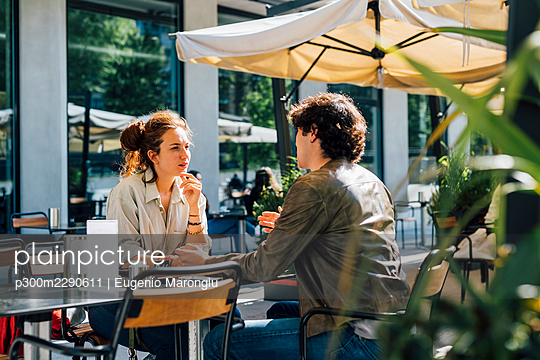 Couple talking while siting at sidewalk cafe on sunny day - p300m2290611 by Eugenio Marongiu
