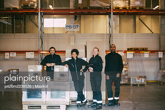 Portrait of smiling warehouse workers standing with box containers - p426m2238536 by Maskot