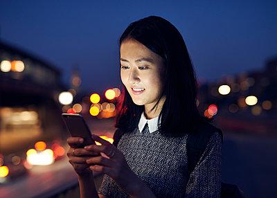 Asiatin mit Smartphone in der Dämmerung - p1124m1169920 von Willing-Holtz