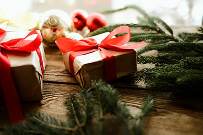 Christmas presents in red ribbon on a wooden background - p1166m2106058 by Cavan Images