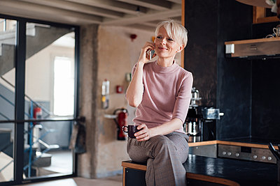 Smiling businesswoman with coffee cup looking away while talking on mobile phone in kitchen at home - p300m2266982 by Robijn Page