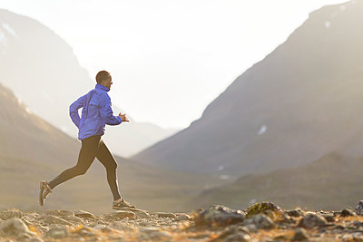Man running in mountains - p312m1521880 by Michael Jonsson