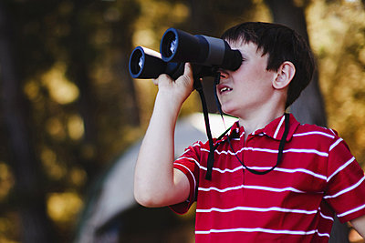 Boy using binoculars at campsite - p42914445f by Hybrid Images