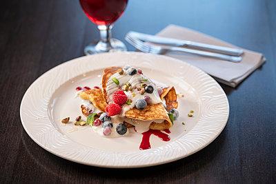 Pancakes with fruit at Italian Restaurant - p429m2078615 by Monty Rakusen