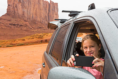 Caucasian girl taking cell phone photograph from car, Monument Valley, Utah, United States - p555m1420823 by Marc Romanelli