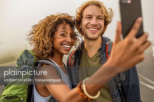 Junges Paar beim Wandern macht ein Selfie - p1355m1574128 von Tomasrodriguez