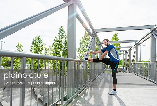Man stetching on a bridge - p300m1587115 von Daniel Ingold