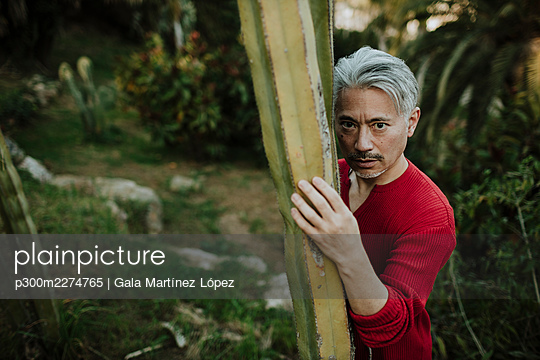 Mature man leaning on cactus in garden - p300m2274765 by Gala Martínez López