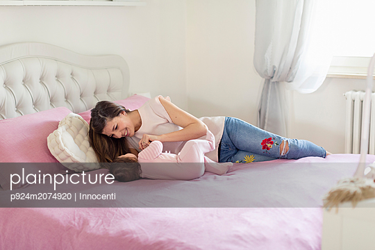 Mother playing with baby girl in bed - p924m2074920 by Innocenti