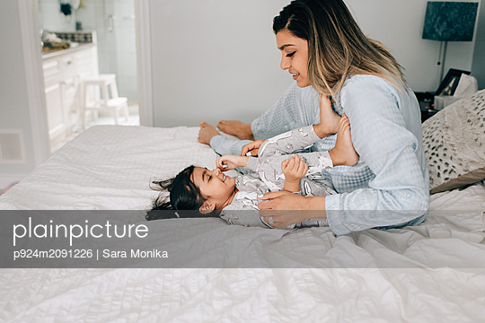 Girl lying by mother on bed in morning - p924m2091226 by Sara Monika