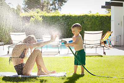 Son spraying water on mother at poolside - p1166m1096103f by Cavan Images