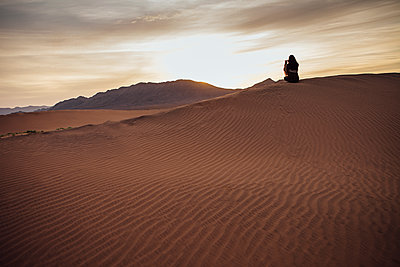 Rear view of woman photographing through mobile phone at desert during sunset - p1166m1473784 by Cavan Images