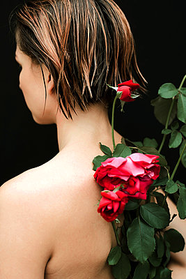 Naked woman with red roses on her back against black background - p1166m2112014 by Cavan Images