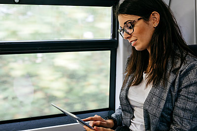 Brunette woman while traveling by train to work, with a tablet in her hands - p300m2155398 by Josep Rovirosa